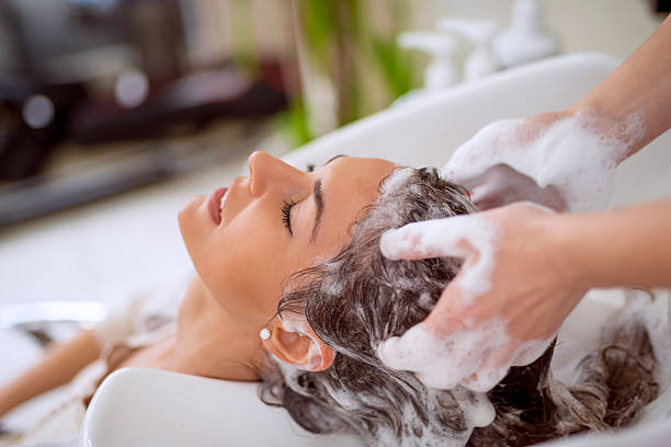 Hairdresser washing hair stock photo
