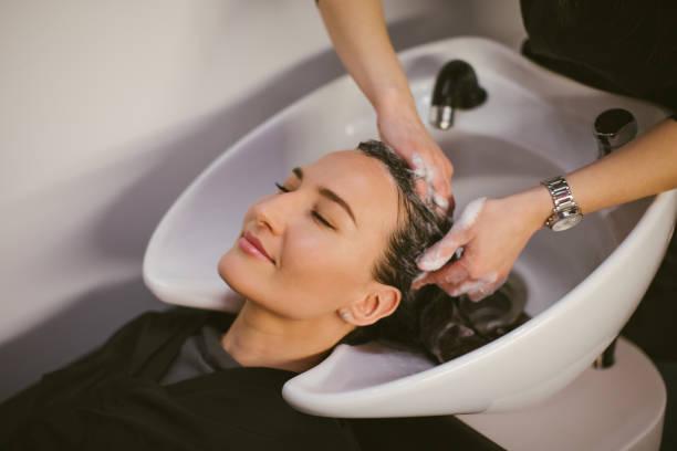 friseur waschen haare an den kunden - brautstyling stock-fotos und bilder