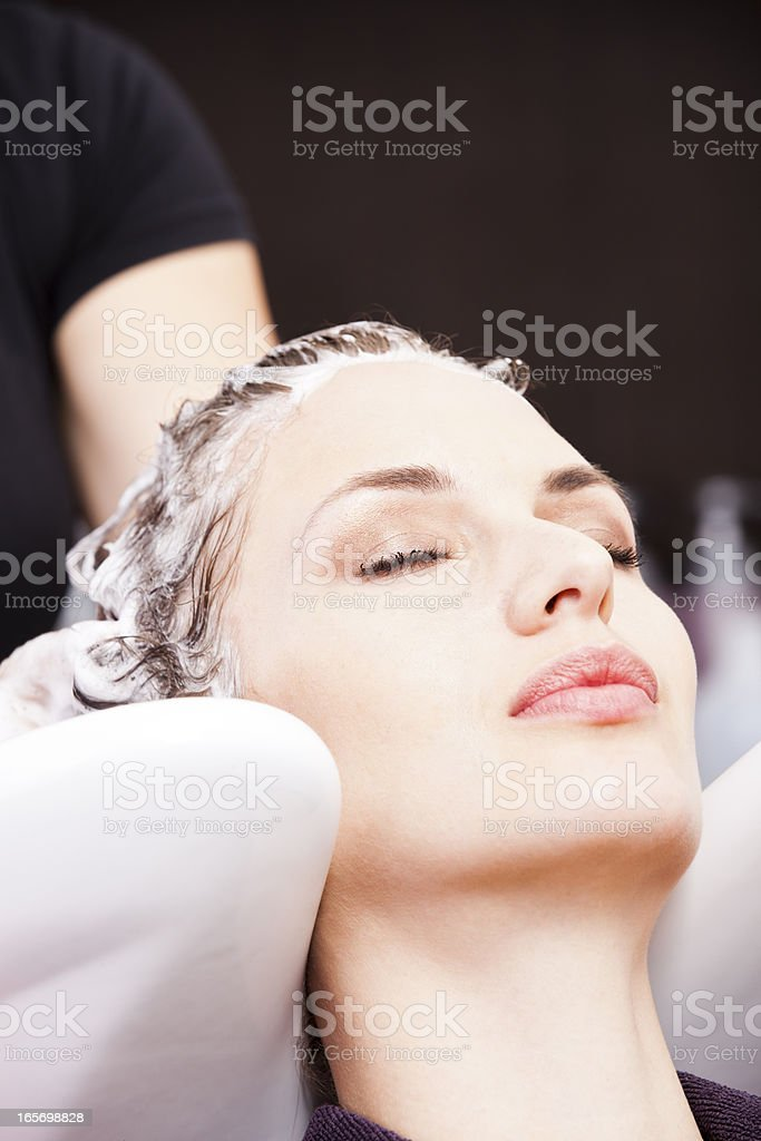 Hairdresser washing woman's hair after coloring royalty-free stock photo