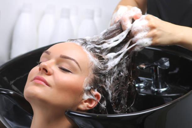hairdresser washing woman's hair in hairdresser salon - lavarsi i capelli foto e immagini stock