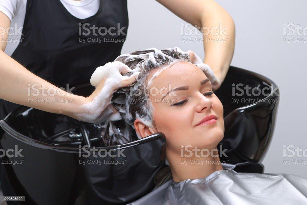 Hairdresser washing woman\'s hair in hairdresser salon