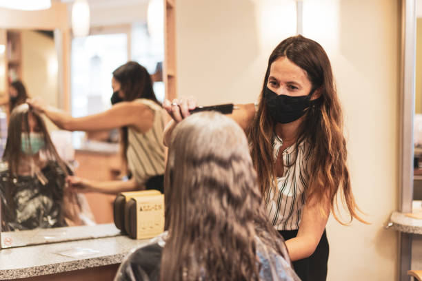 hairdresser with mask enjoying to work again in her hair salon after lockdown is over - covid hair imagens e fotografias de stock