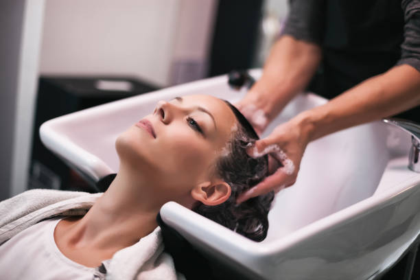Hairdresser working in his studio Young woman getting new hairstyle at professional hair styling saloon. Hairdresser is massaging her head. saloon stock pictures, royalty-free photos & images
