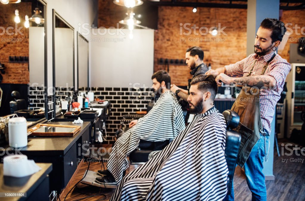 Hairdressers cutting hair of clients in salon stock photo