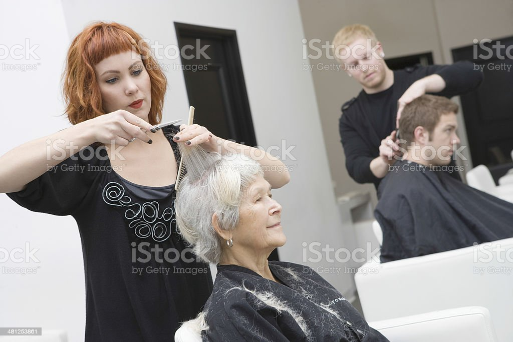 Hairdressers Giving Haircut To Customers stock photo