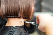 istock Hairdresser's hands are cutting brown short hair. 1186053045