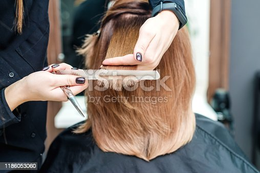 Hairdresser's female hands are holding woman's red hair with comb between fingers in the beauty salon close up.