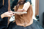 istock Hairdresser's hands are holding red hair in the beauty salon. 1186053060