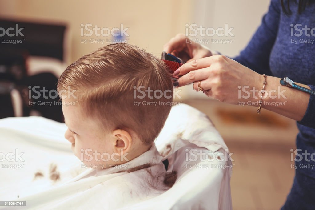 Hairdressers Hands Making Hairstyle To Little Boy Close Up