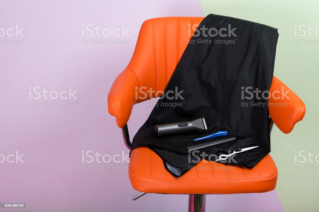 hairdresser's set for shaving hair, on an orange chair, there is a place for an inscription - foto stock