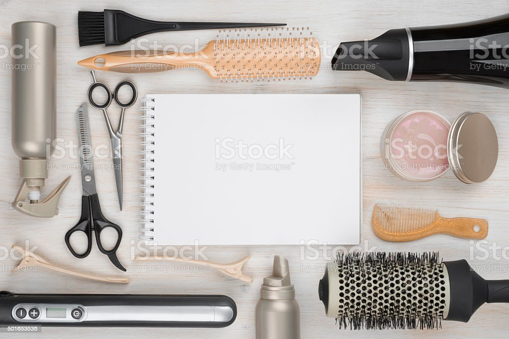 Hairdressing tools on wooden background with blank sheet in centre stock photo