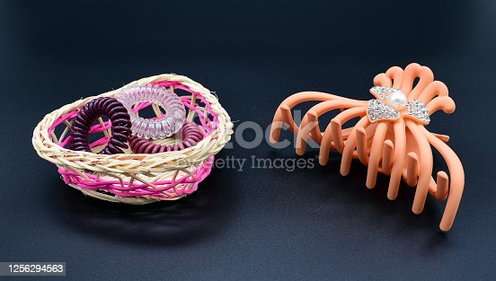 Elastic bands for hair in a wicker basket and a hairpin on a black background.