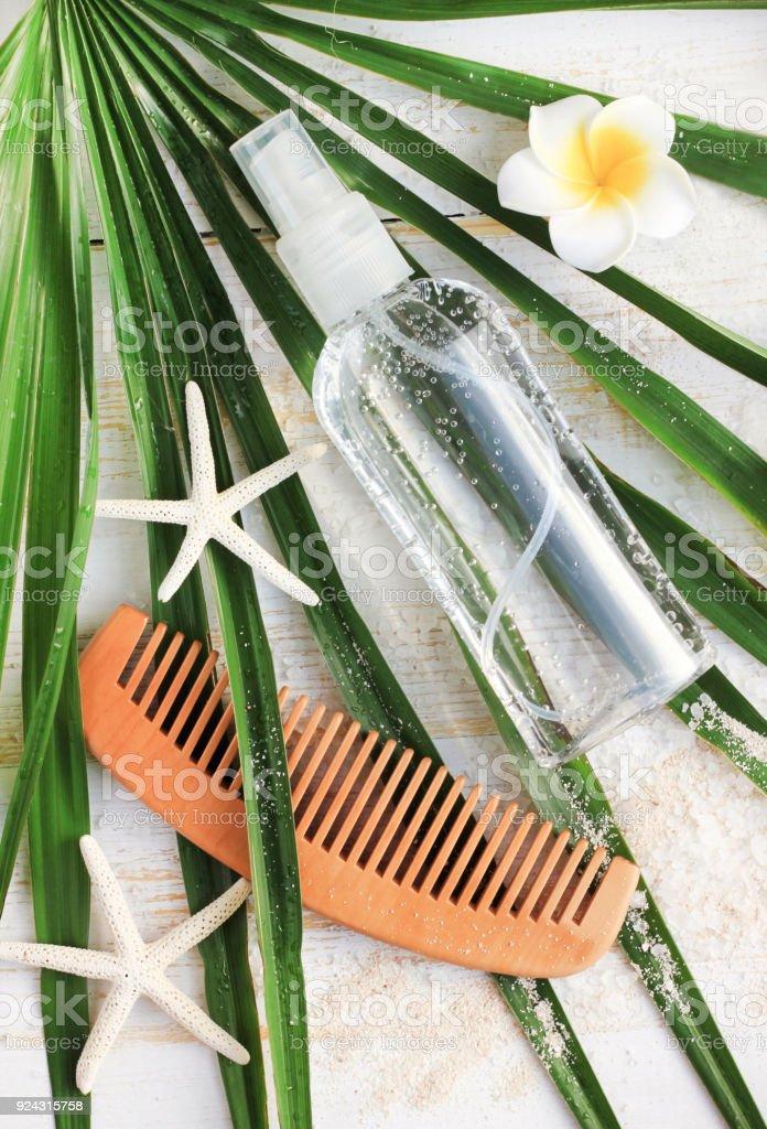 Hairspray with epsom salt on palm leaf, vertical. stock photo