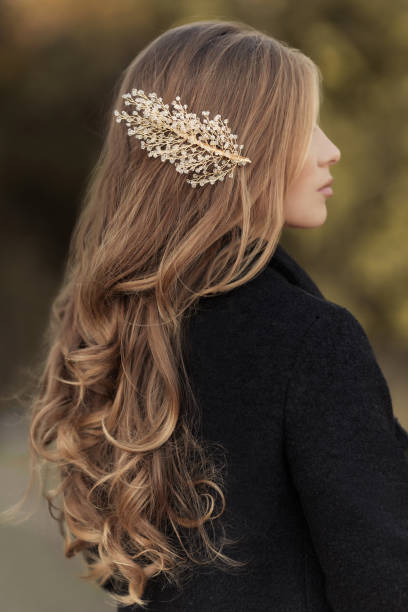 Hairstyle of long hair curly blonde with handmade gold hairpin stock photo