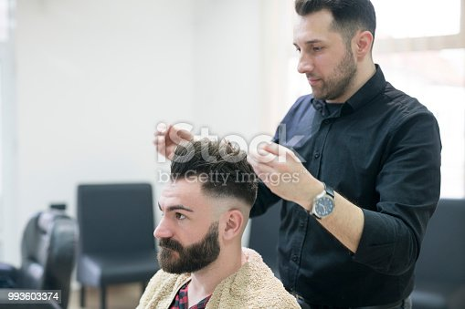 Hairdresser making stylish haircut