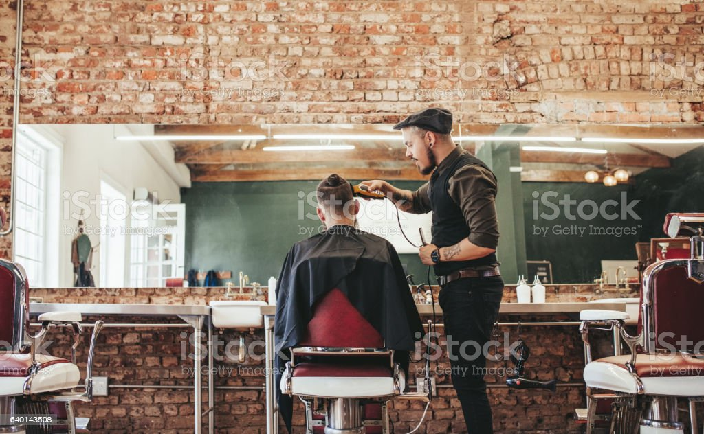 Hairstylist cutting hair of male customer - fotografia de stock