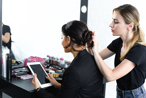 hairstylist doing hairstyle while businesswoman in suit using digital tablet