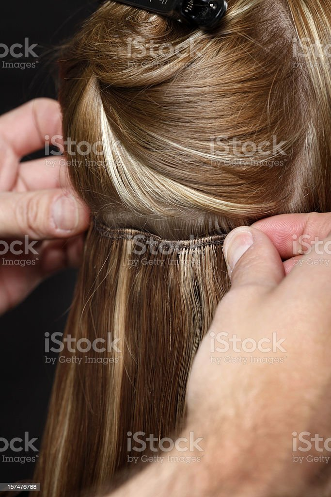 Hairstylist Putting in Hair Extensions royalty-free stock photo