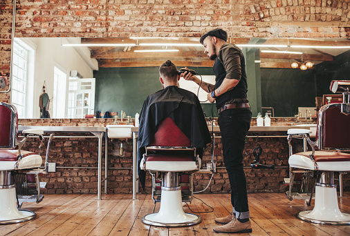 istock Hairstylist serving client at barber shop 639607852