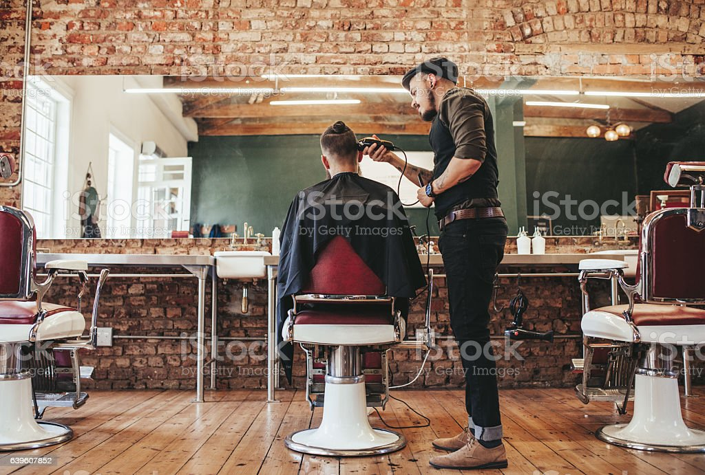 Hairstylist serving client at barber shop - fotografia de stock