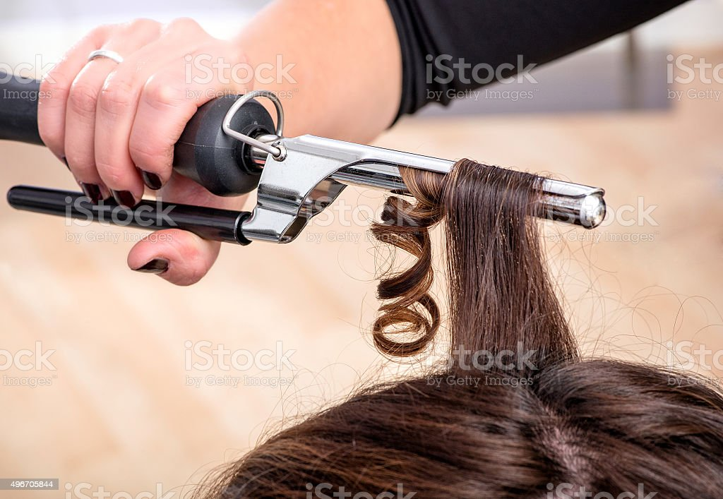 Hairstylist using a curling iron or tongs stock photo