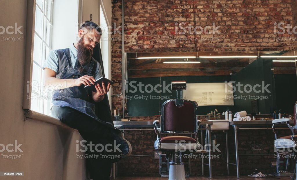 Hairstylist using digital tablet at his shop stock photo