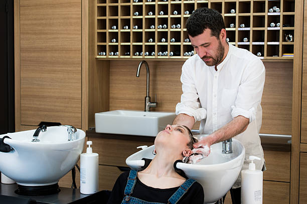 Hairstylist washing head to the young woman at the hairdresser stock photo