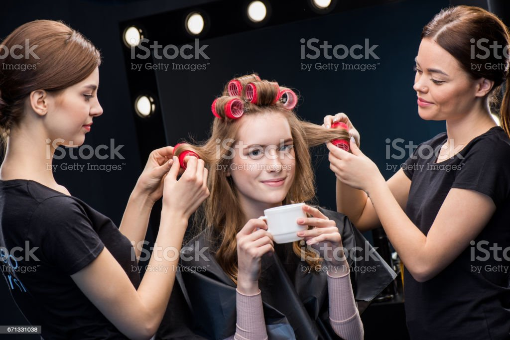Hairstylists curling hair to woman stock photo