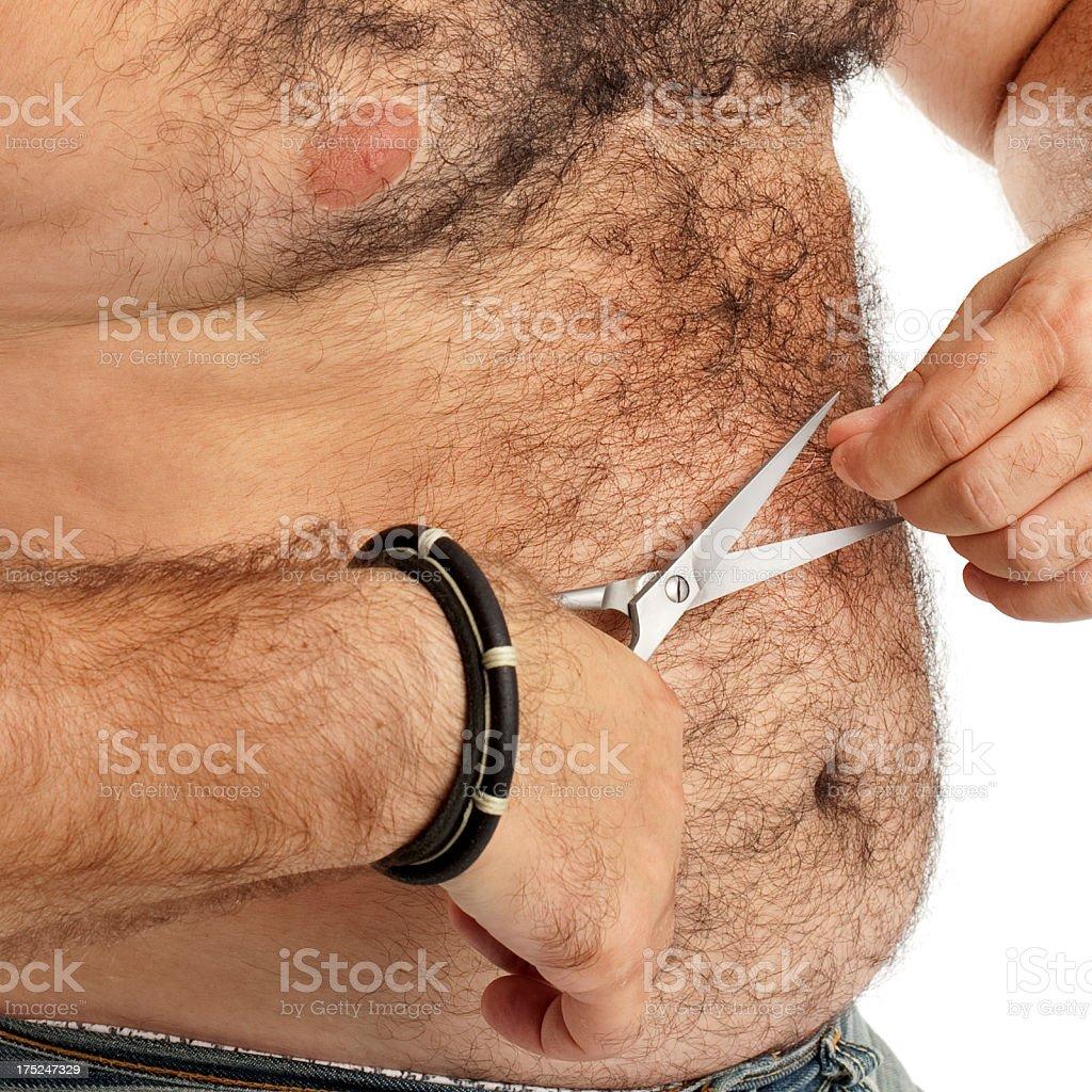 Hairy man cutting own body hair stock photo