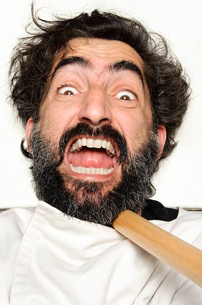 Hairy man on the floor being attacked with a stick stock photo