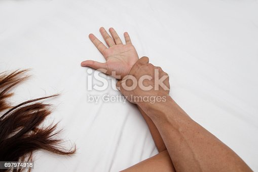 istock A hairy man's hand holding a woman hand for rape and sexual abuse concept 697974918