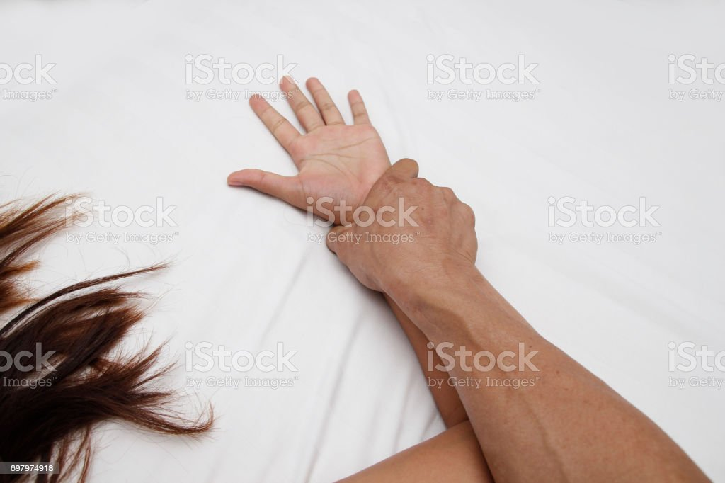 A hairy man's hand holding a woman hand for rape and sexual abuse concept stock photo