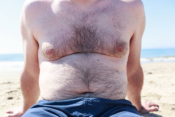 hairy, overweight tourist at the beach - stomach sitting stock photos and pictures