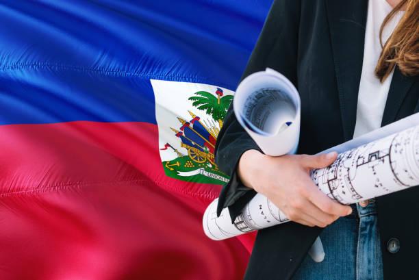 Haitian Architect woman holding blueprint against Haiti waving flag background. Construction and architecture concept. Haitian Architect woman holding blueprint against Haiti waving flag background. Construction and architecture concept. Haiti Flag stock pictures, royalty-free photos & images