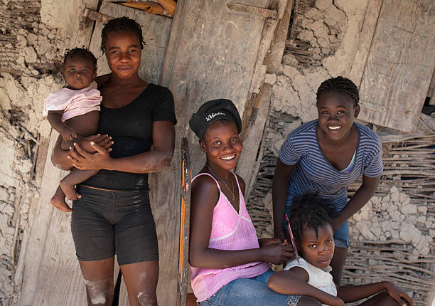 Haitian family in front of their house Chambrun, Haiti, March 08, 2011: This family is living in a poor village. The houses are built out of clay and wood, but they did resisted the earthquake in 2010. haitian ethnicity stock pictures, royalty-free photos & images