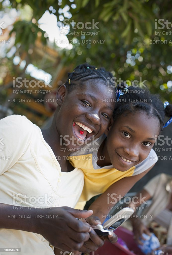 Haitian girls having fun with mobile phone stock photo