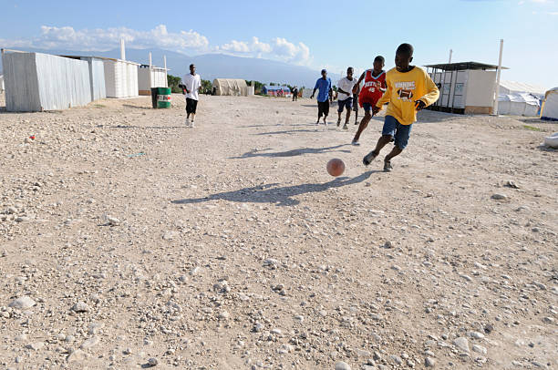 """Haitian Kids. """"Port-Au-Prince, Haiti - August 30, 2010: Young Haitian adults playing soccer which is one of their favorite sport inside their tent cities ."""" haitian ethnicity stock pictures, royalty-free photos & images"""