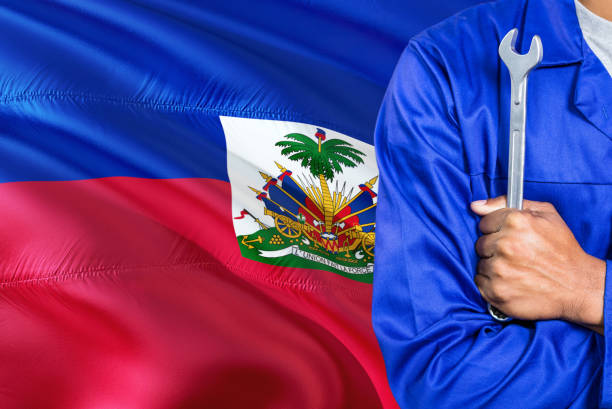 Haitian Mechanic in blue uniform is holding wrench against waving Haiti flag background. Crossed arms technician. Haitian Mechanic in blue uniform is holding wrench against waving Haiti flag background. Crossed arms technician. Haiti Flag stock pictures, royalty-free photos & images