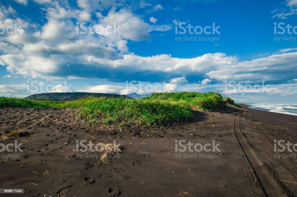 Playa de Halaktyr. Kamchatka. Federación de Rusia. Color casi negro de la arena playa del océano Pacífico. Montañas de piedra y hierba amarilla están sobre un fondo. Luz azul cielo - Foto de stock de Agua libre de derechos