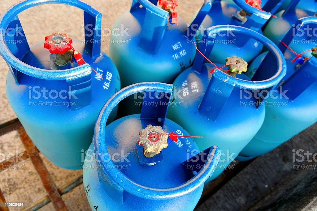 Half a dozen blue propane tanks stock photo