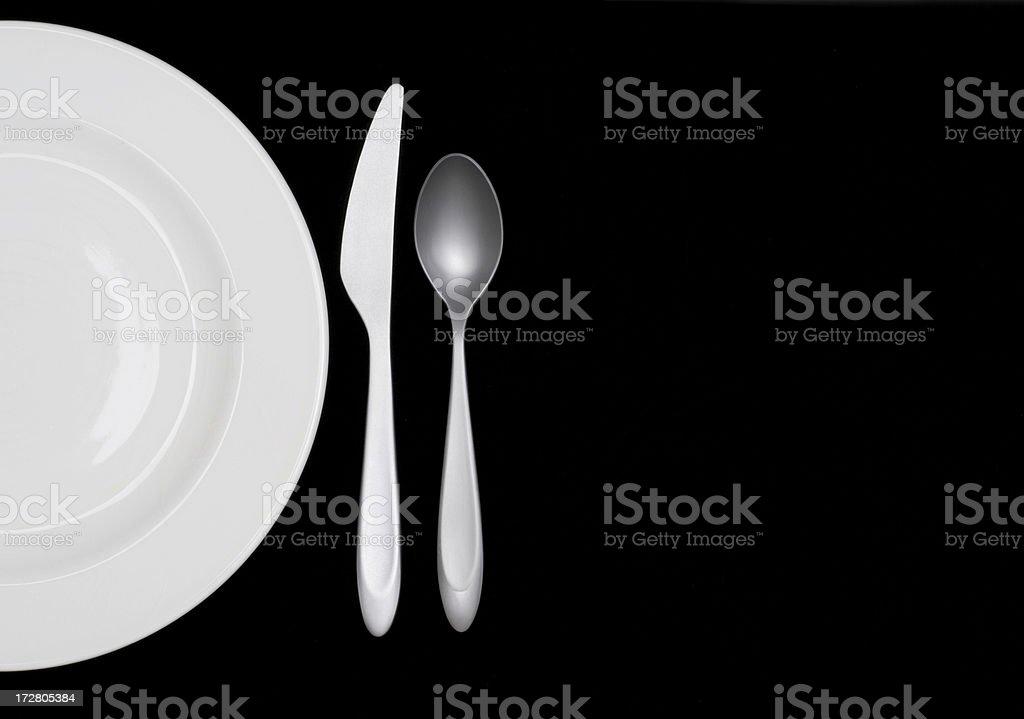 Half a white plate on black w silverware royalty-free stock photo