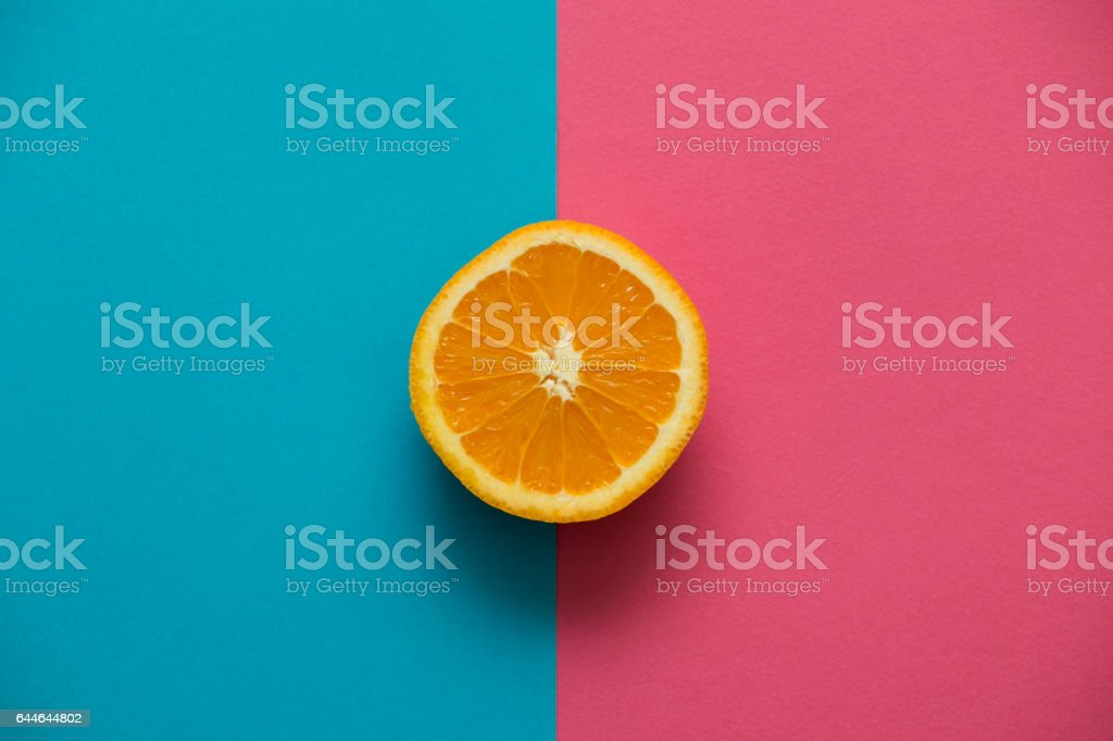 Half an orange on rose  blue background. Directly above view. stock photo