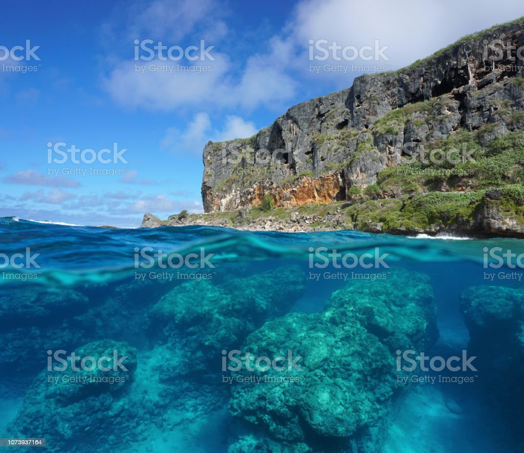 Half and half coastal cliff and rocks underwater стоковое фото