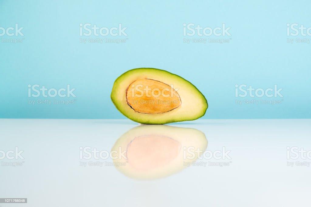 Half avocado fruit on white table stock photo