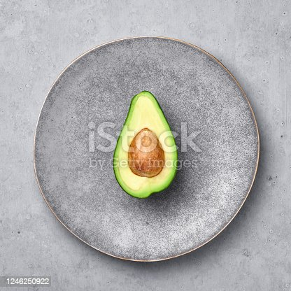 Half Avocado in gray hand made matte plate on concrete rough backdrop. Grey ceramic saucer setting.