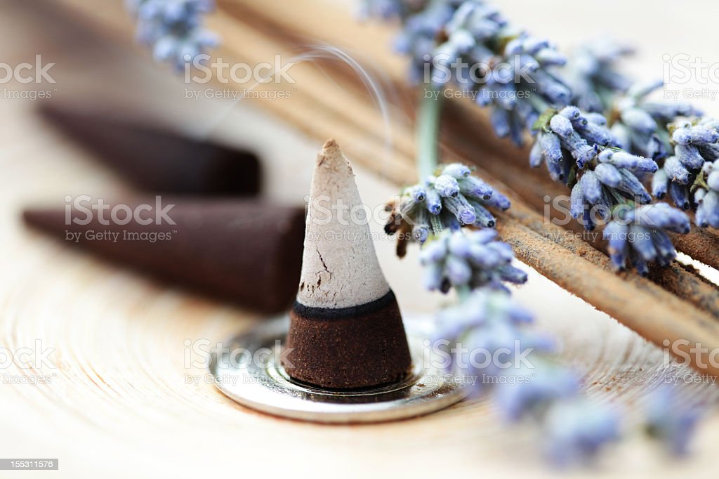 Half burned incense cone on metal circle with lavender stock photo