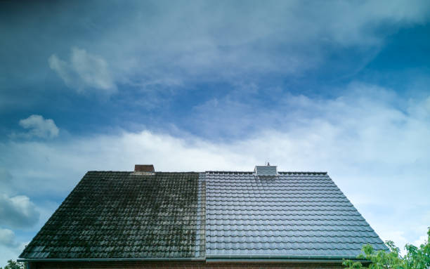A half cleaned house roof shows the before and after effect of a roof cleaning. stock photo