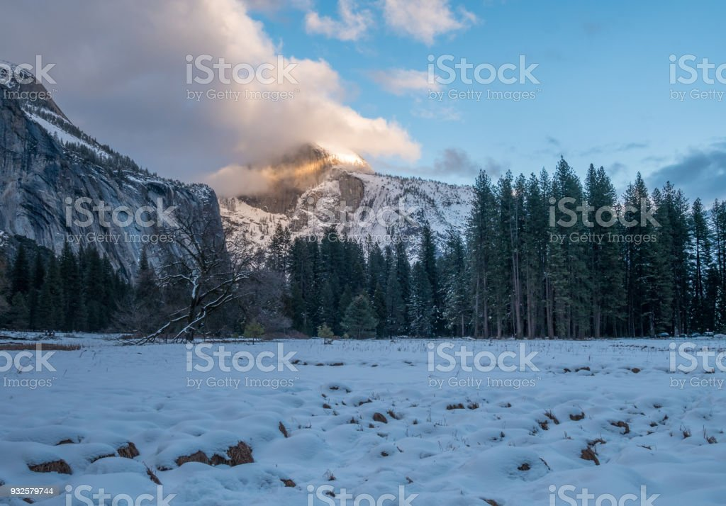 Half Dome Peak With Low Clouds Shinning with Sunset Light stock photo