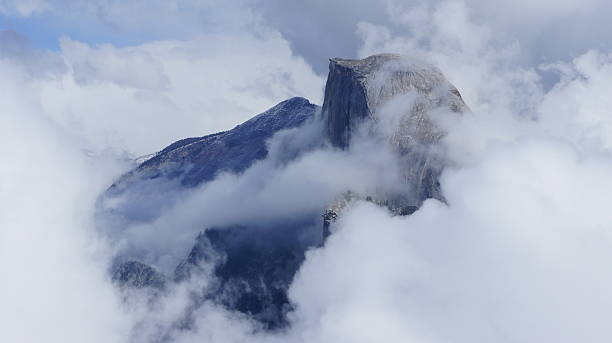 Half Dome surrounded be white clouds stock photo