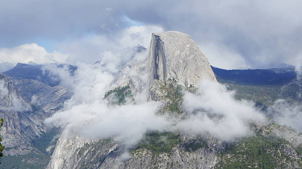 Half Dome Surrounded by White Clouds in Yosemite stock photo